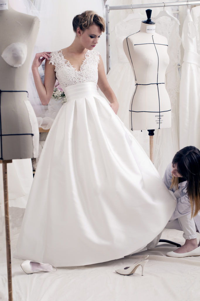 Bride in floor length, white satin, wedding dress with lace bodice and short sleeves having the skirt of her dress altered
