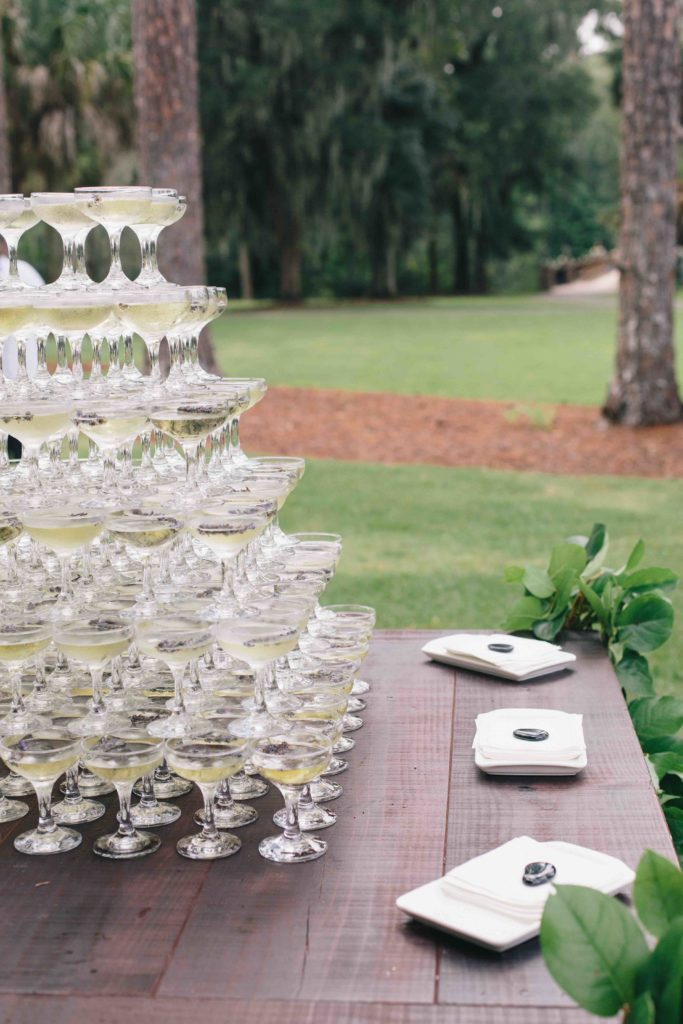 A pyramid of champagne glasses on a dark wood table in a well maintained garden