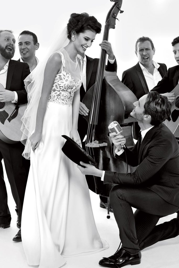 Bride in floor length, white dress stands in front of a band while the groom sings to her on one knee