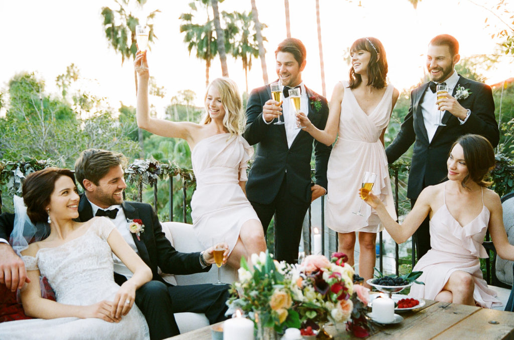 Five people in formal outfits toasting champagne to a seated bride and groom outside on a balcony