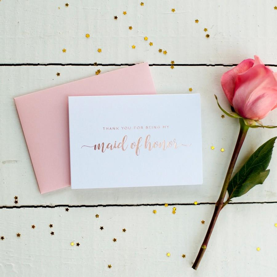 "A white card with rose gold calligraphy stating ""Thank you for being my maid of honor"" sitting on top of a dusty pink envelope. Beside that is a pink rose, this is sitting on top of a white wooden table and scattered with gold star confetti"