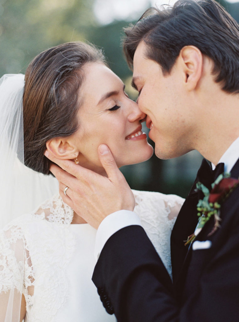 Close up shot of a dark haired bride in floor length, white wedding dress and white veil kissing her dark haired husband in a black tuxedo