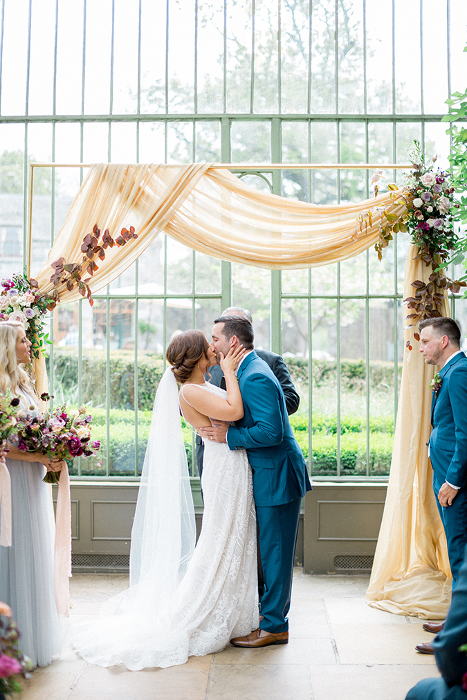 Dark haired Irish bride in floor length, white wedding dress kisses her dark haired Irish husband in a blue suit, they are photographed at the head of an altar and appear to be having their first kiss as a married couple