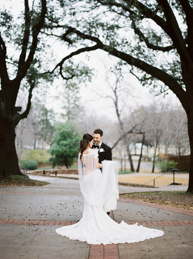 Dark haired bride in floor length, white wedding dress embraces her dark haired husband in a black tuxedo, they are posed in a park and framed by trees