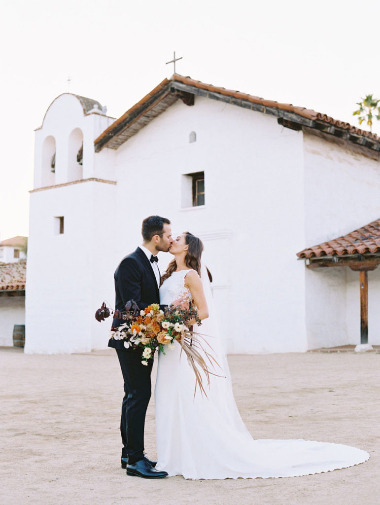 Dark haired bride in floor length, white wedding dress kisses her dark haired husband in a black tuxedo, they are in front of a small, white, Spanish style chapel