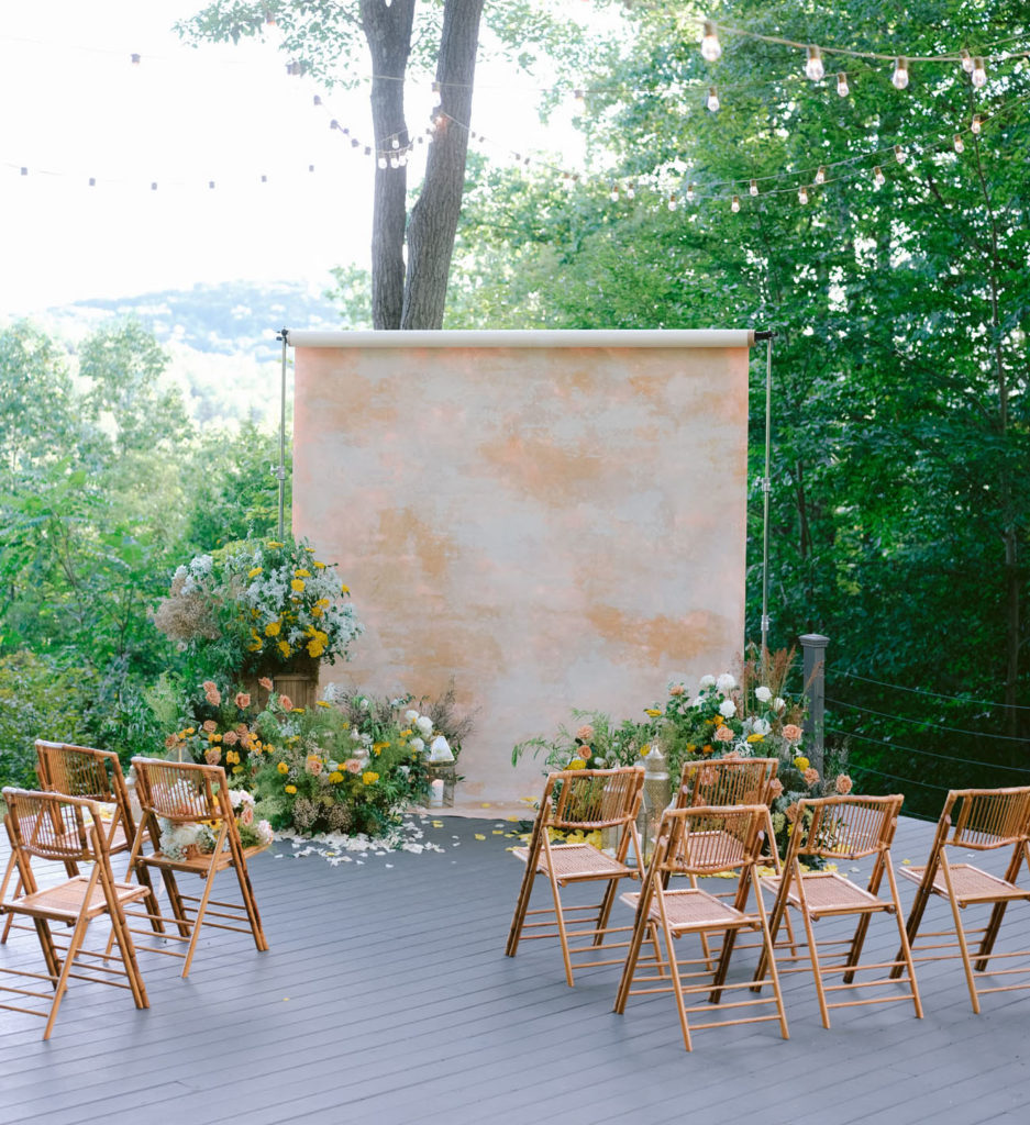 A large role of brown, white and gold butcher paper acts as the backdrop to a small wedding. In front of the paper are several large barrels overflowing with pink, white, yellow and green flowers. Among the flowers are lanterns. In front of the flowers and paper are eight wicker folding chairs