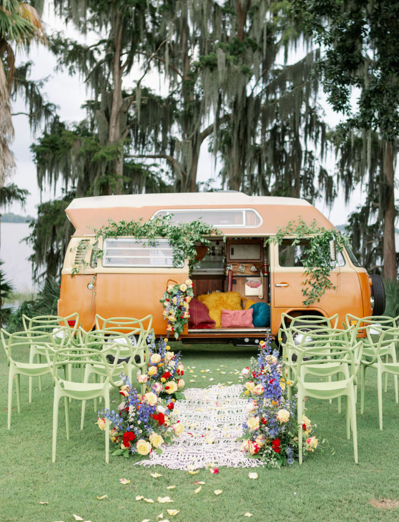 Orange van with open doors is decorated with yellow, red, purple and green flowers sits at the end of a small white crochet aisle. In the background are tall handing trees and the ocean