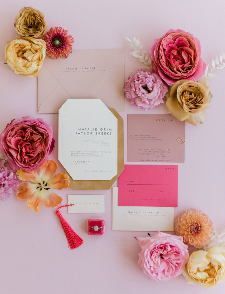 Pink, white and gold stationary is laid out on a light pink table and decorated with pink and yellow flowers. At the bottom of the image is a wedding ring in a small red box