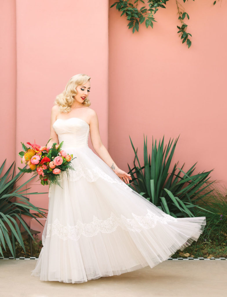 Blonde bride in a floor length white wedding gown, holding a large bouquet of flowers. In her hair she has a large gold and pearl clip sweeping her curls into a structured vintage pin-curl hairdo