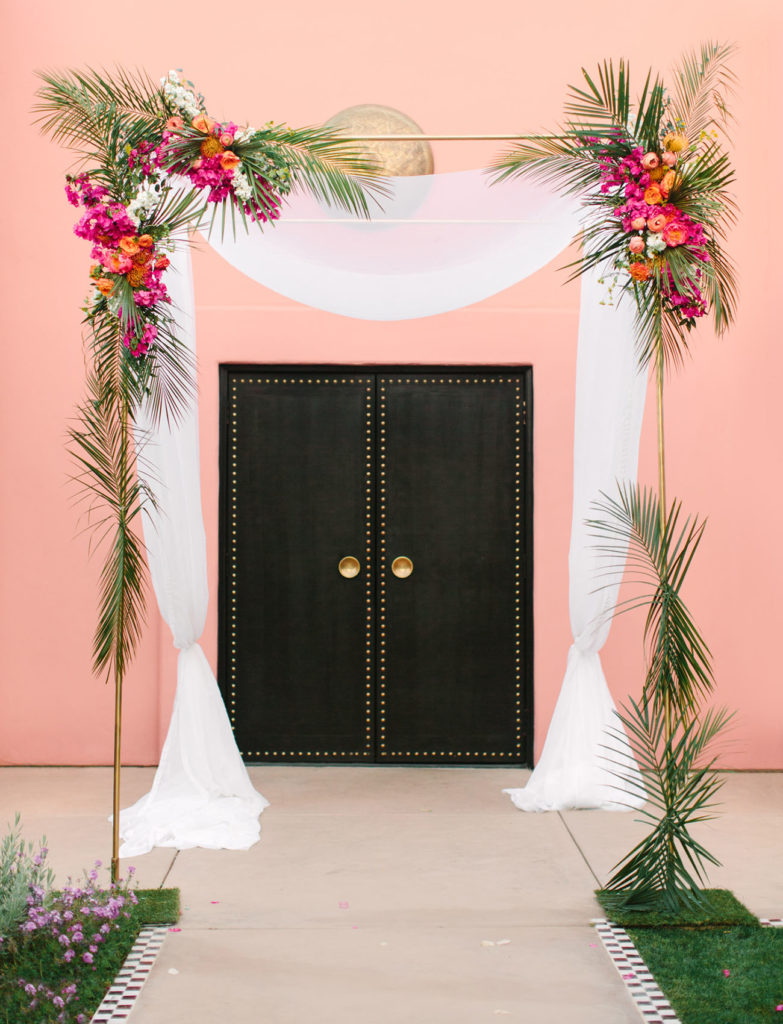 Delicate gold frame arch decorated with a long hanging white sheet and blooms of pink and white flowers, ferns and leaves adorn the top and sides. Behind the arch is a pink wall and a large black door