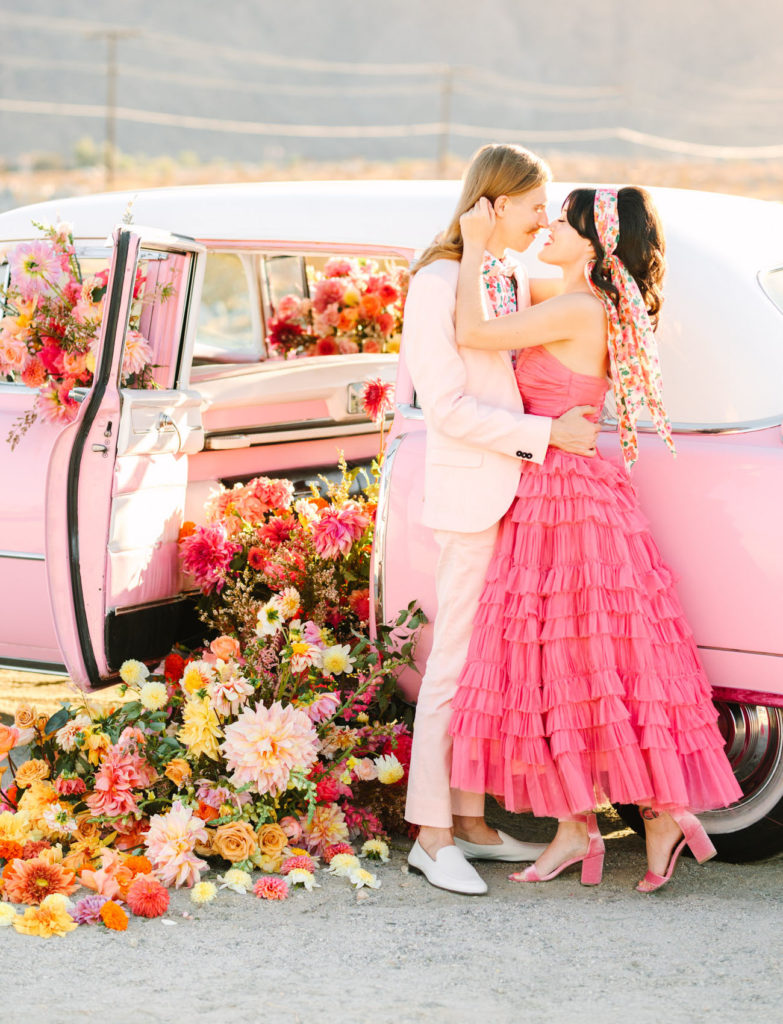 Bride in pink ruffled midi-length dress embracing groom in powder pink suit. They are leaning against a powder pink cadillac car filled with flowers that are spilling out of the open car door